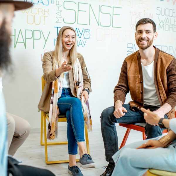 Group of young and happy people sitting together in a circle during the psychological therapy in the office